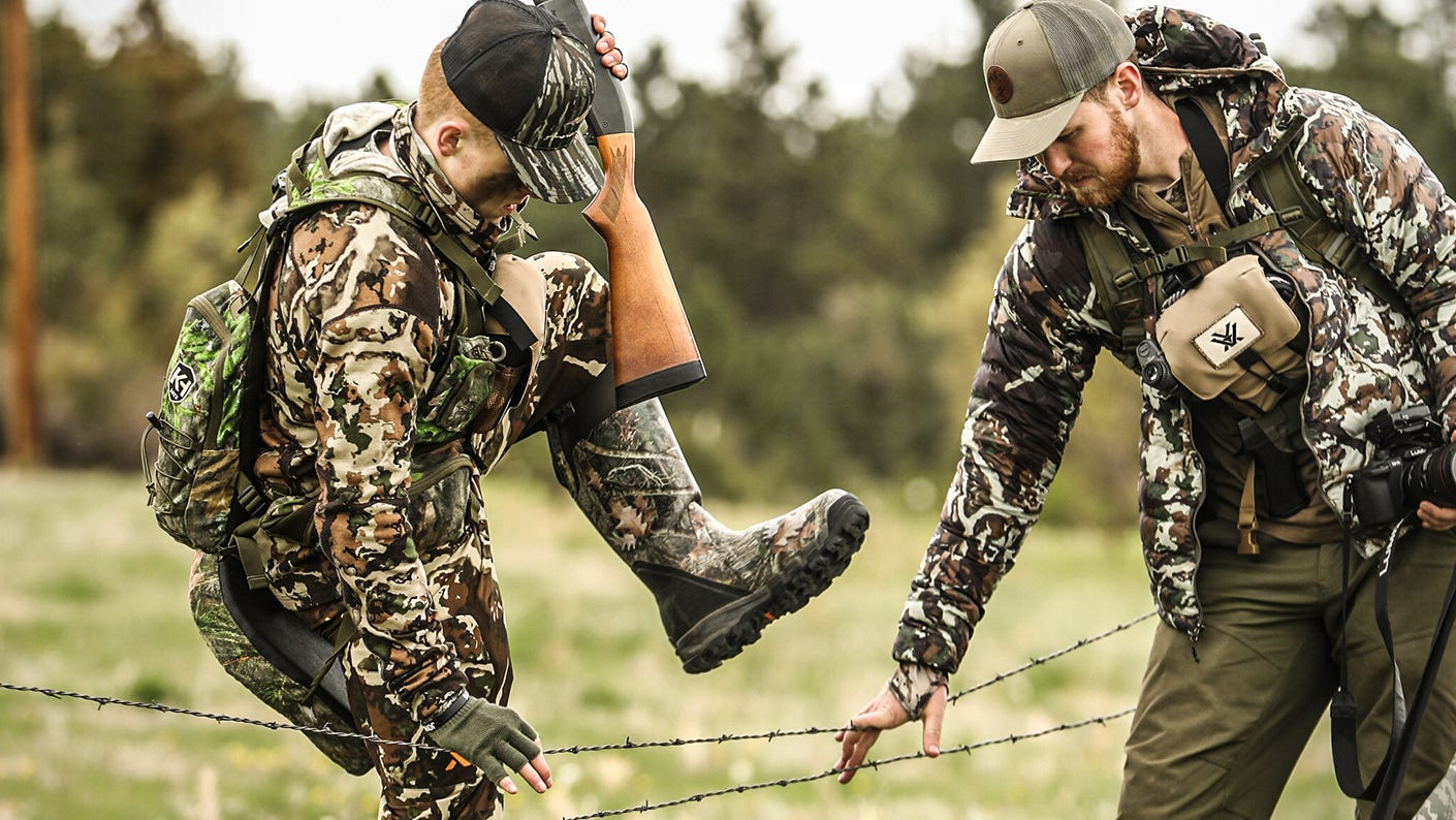 Hunting mentor helping new hunter cross a fence.