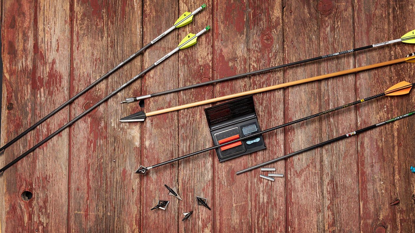 Array of bows and arrow tips on barn board