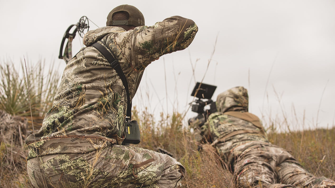 Two bowhunters stalking deer. in a field.