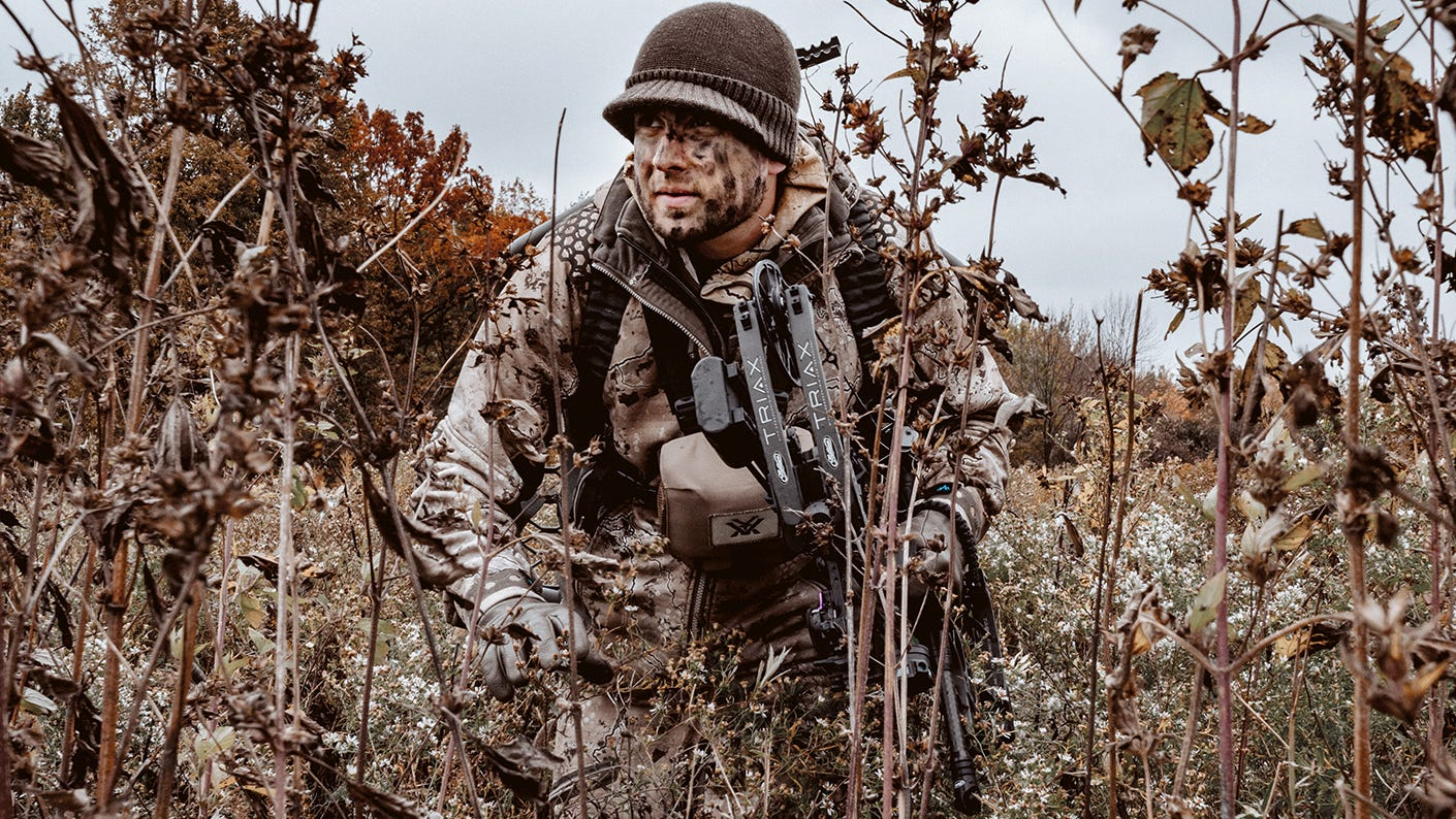 Bow hunter in a field scouting for deer.