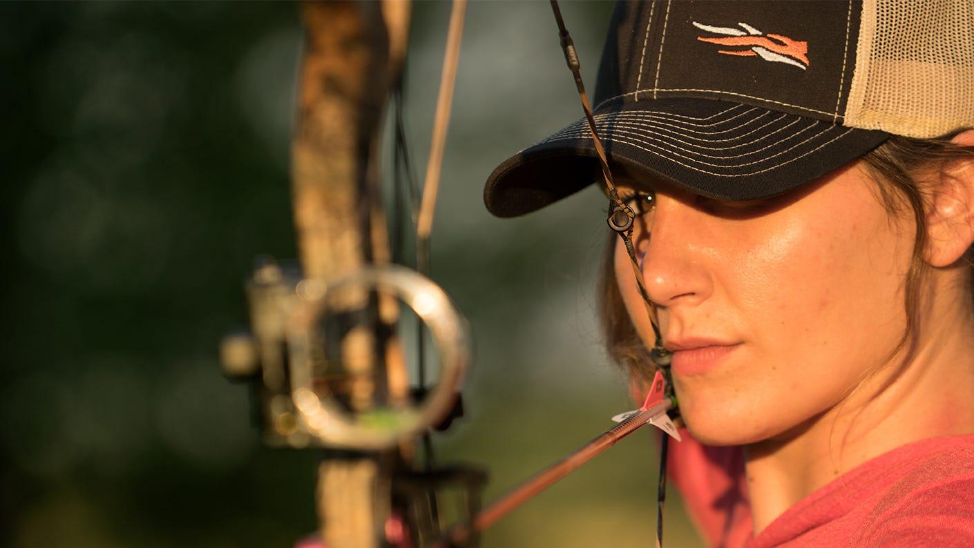 Bow hunter drawing back bow string.