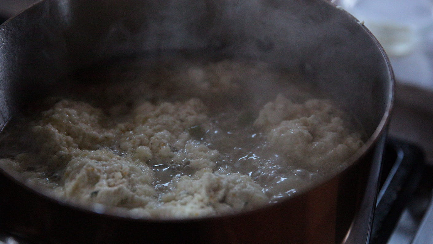 Game bird dumplings bubbling in a stock pot.