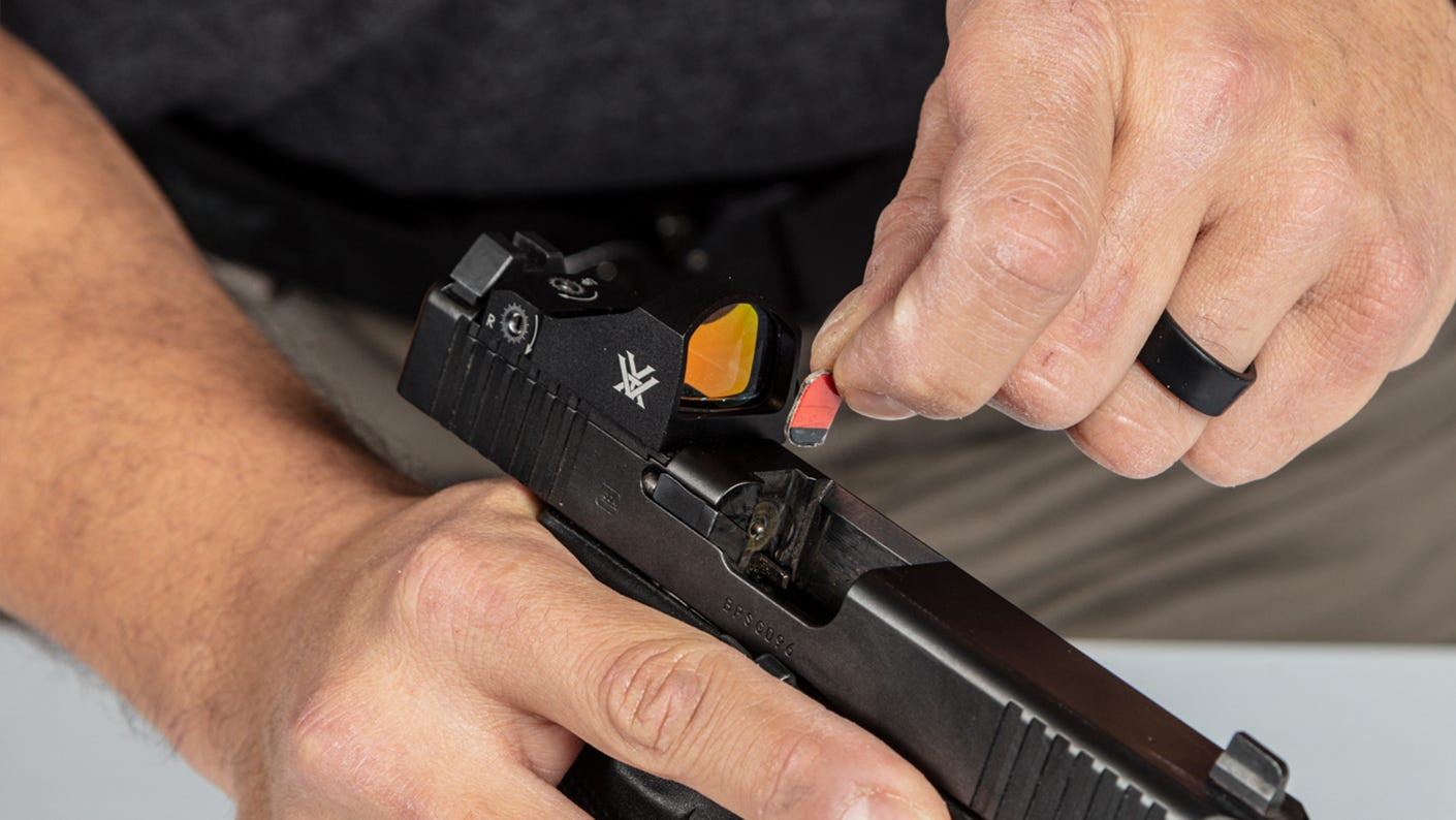 Inserting a small piece of cardboard to keep your gun out of battery.