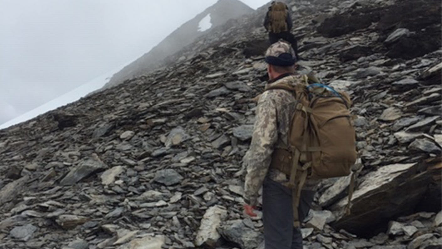 Hunter and guide on mountain in conditions that are less than ideal.