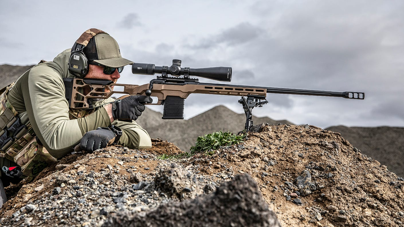 Shooter aiming rifle in rocky landscape.